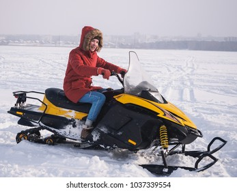 Girl in the snowmobile. Winter snow field.