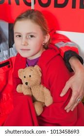 Girl snuggled up in blanket at ambulance
