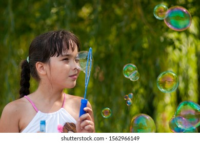 Girl and soap bubbles outdoor at sunrise