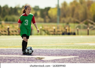 Girl at a soccer practice running with the ball