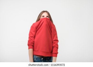 A girl with a social phobia hides her face in a sweater. She looks frightened at the camera