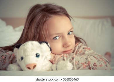 girl with soft toy in bed