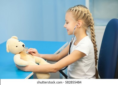 The girl with a soft toy in the hospital on a background of ultrasound machines, smiling and playing