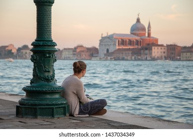 Girl solo traveler in Venice, Italy sitting by the canal alone, listening to the music and looking at the Church of the Santissimo Redentore in the distance. Peaceful evening by the sea, after sunset.