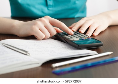 girl solving a math problem in notepad on table