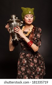 Girl in soviet retro style posing with samovar. Girl with a green cap on his head. Star on the cap.