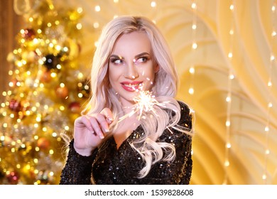 The girl with the sparklers . Charming blonde in the new year, holding sparklers, on the background of a Christmas tree in Golden color .