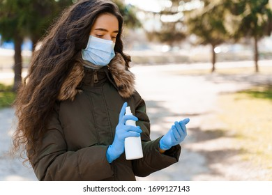 Girl spays antiseptic on her hand to desinfection. Life style photo of women in medical mask and medical gloves. Stop coronavirus covid 19