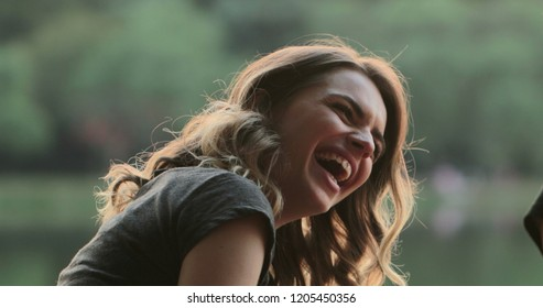 Girl speaking to friend in conversation, burts laughing out loud to friend joke. Real life authentic smile and spontaneous laugh