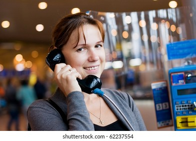 The girl speaks by phone at the airport