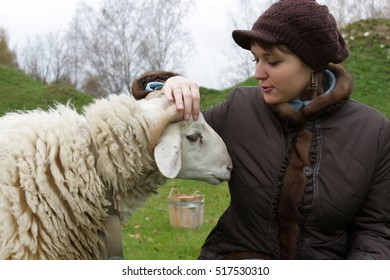 The girl speaks with a sheep on lawn