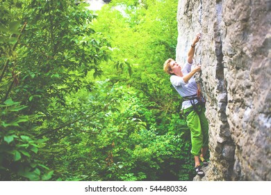 The girl spends time actively engaged in climbing, young woman climbing on a rock in a forest.