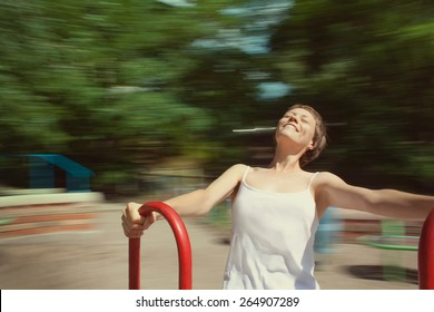Girl spinning on the carousel, very happy. Head is spinning and the world around is blurred. Happy life, smiling girl and blurred background on the photo.