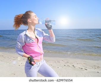 Girl sports drinks water from the bottle near the ocean in hot weather