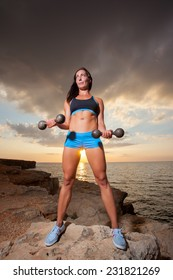 The girl with a sports figure does exercises with dumbbells