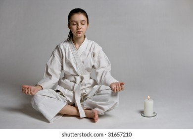 The girl in a sports kimono in a relaxation pose
