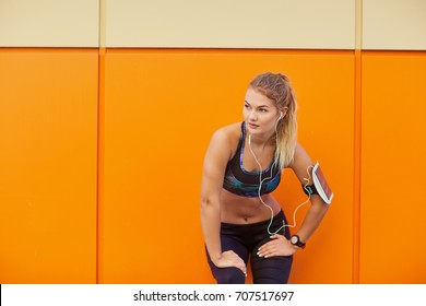 Girl sports listening to music with headphones on orange backgro