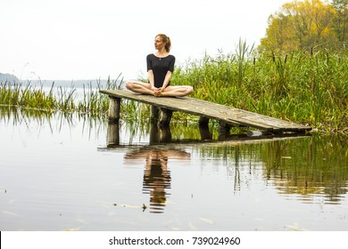 Girl with a sports sexy figure is engaged in Meditation, relaxation, balance, calmness yoga on background of a calm autumn river lake. Girl is reflected in water.