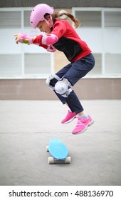 Girl in a sports suit with pink helmet jumping with skateboard in street