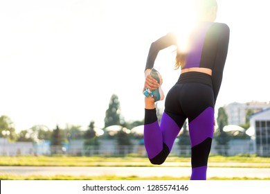 girl sportsman crossfit and squats agains at sunset in the stadium