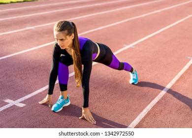 girl sportsman squats at sunset in the stadium