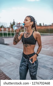 The girl in sportswear. In his hand, a smartphone listens to music on headphones. Drinks cold and clean water from a bottle. Beautiful Tattoos on tanned female skin. Rest after a hard workout.