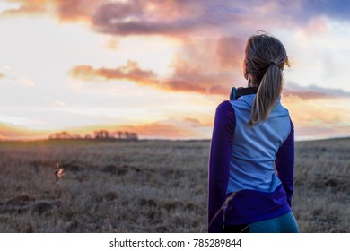 Girl in a sportswear stands on the field and looks on a breathtaking sunset. Winter season sunset. Photo has a freedom concept