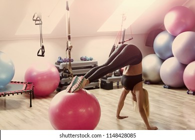 Girl in sportswear training on fitball in gym. Woman athlete do handstand with legs on fit ball. Balance, endurance, strength concept. Sport, fitness, yoga. Workout, training, activity.