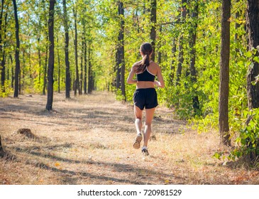 girl sportswoman running in the park with a dog