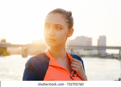 a girl in a sporty uniform stands against the background of a river