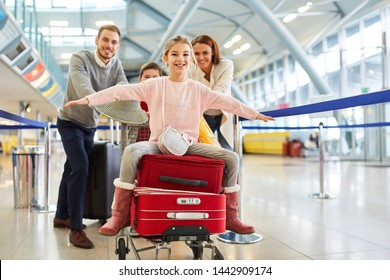 Girl spreads her arms and sits on suitcases before departing at the airport terminal