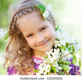 Girl at spring park. Little girl with branches blossoming apple tree