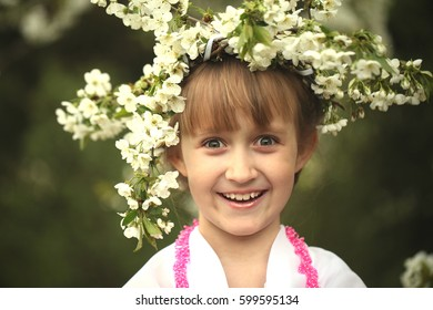 The girl is spring. Wreath of cherry blossoms on the head of a teenager. Funny facial expression. Wonder in a white dress.