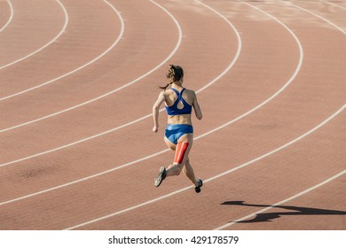 girl sprinter runs through stadium. feet taping