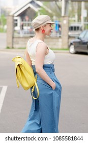 Girl in square hat, white t shrt and blue wide pants walking at car parking
