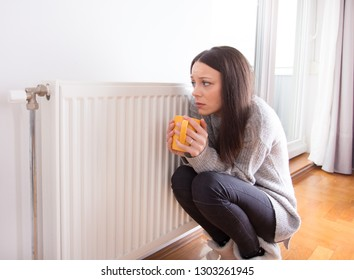 Girl squatting beside radiator with cup of hot tea in hands and trying to warm up