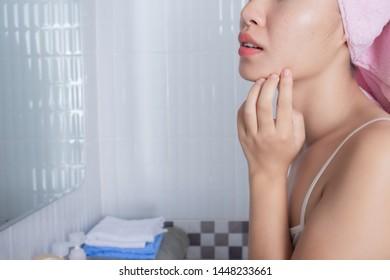 Girl squeezes facial acne in the bathroom.
