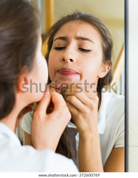 Girl squeezing pimple at the home