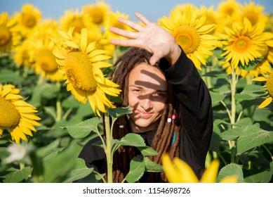girl squinted from the sunlight among the sunflowers in the field. A happy hippie with dreadlocks travels in the summer