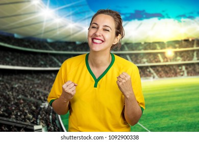 Girl in stadium cheering for Brazil with the hope that the brazilian team will win the mundial along with the other fans of the world. Crowded stadium and fan celebrating victory in the cup soccer