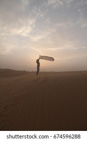 a girl stand with here scarf, in desert dune, evening cloud sky background