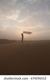 a girl stand with here scarf in hand, in desert dune, cloud sky background