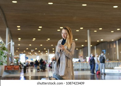Girl standing in airport waiting room with valise and using smartphone. Concept of traveling abroad and communication by mobile phone, free hotspot.