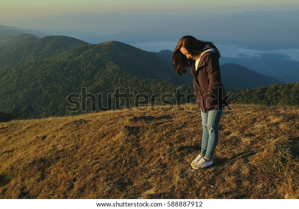 Girl standing alone on top mountain in winter good morning time with sunrise light
