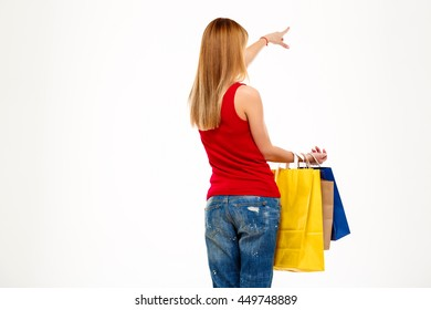 Girl standing back to camera with purchases over white background.