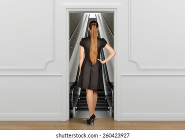 Girl standing back to doorway going on escalator.