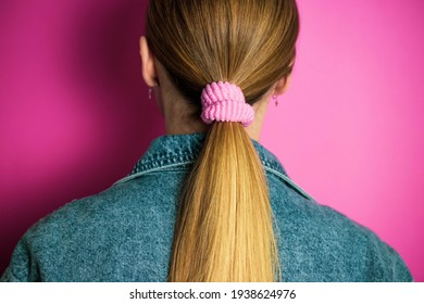 Girl standing back with tied ponytail on the head