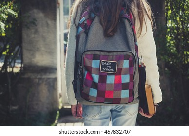 Girl standing with a backpack for school and book