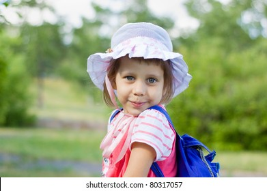 girl standing with a backpack, smiling, summer