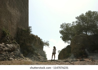 Girl standing between the trees near a castle wall.
